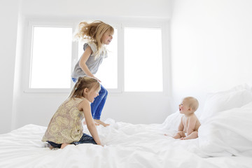 Baby boy sitting on a bed with two girls, kneeling and jumping.