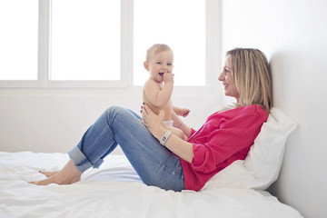 Blond woman wearing red top and jeans lying on a bed, baby girl sitting on her lap.