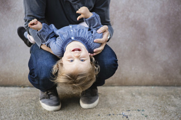 Man holding young girl upside down on his lap