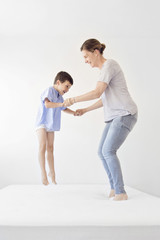Smiling woman and boy holding hands, jumping on a bed.