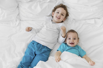 High angle view of boy wearing blue trousers and baby boy wearing blue T-shirt on a bed.