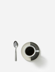 Morning coffee served on saucer with silver spoon