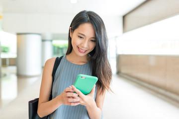Woman looking at smart phone at street