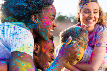 happy young multiethnic couples with colorful paint on clothes piggybacking at holi festival
