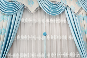 Part of beautifully draped curtain on the window in the room. Close up of curtain drapery with pendants. Luxury curtain, home decor. Turquoise and blue panels. Lace drapery