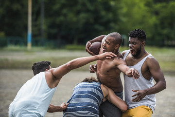 group of young multicultural men playing football on court