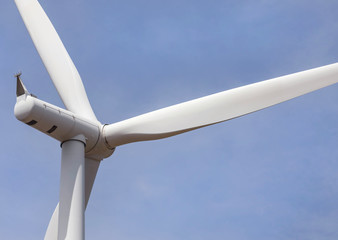 close up wind turbine generating electricity producing alternative energy with blue sky background