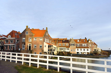 View from the bridge in Enkhuizen (city in Netherlands) traditional old brick buildings with tile roofs