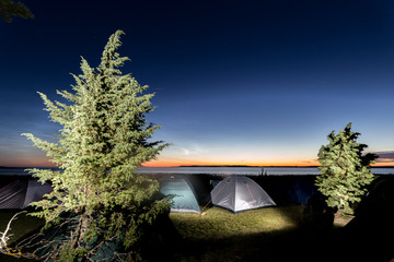Twilight over sea with many camped tents