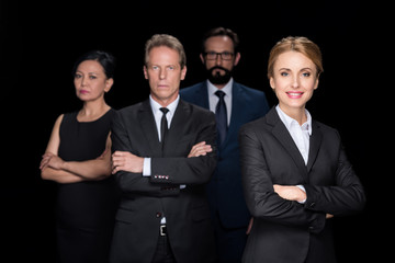 confident multiethnic group of businesspeople standing with crossed arms and looking at camera isolated on black