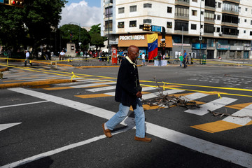 People walk in an empty street during a strike called to protest against Venezuelan President Nicolas Maduro's government in Caracas
