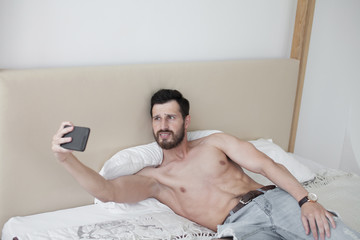 Handsome shirtless muscular bodybuilder man in jeans taking selfie with cell phone while laying on bed. Sexy bearded man.