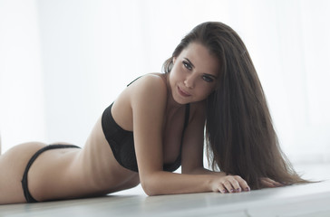 The erotic photo shoot in black lingerie on the tanned sexy girl. Tanned girl in a candid underwear at a photo shoot. erotica. Passion. Orgasm. Sex. Ecstasy.
