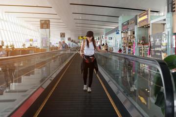traveller woman on travelator at international airport.