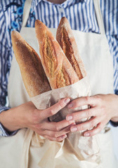 Close-up image of woman holding package of fresh baguettes.