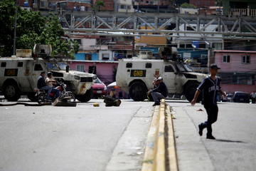 People pass by a street blocked by riot security forces during a strike called to protest against Venezuelan President Nicolas Maduro's government in Caracas