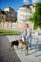 Couple in love with two dogs pit bull terrier on a walk.