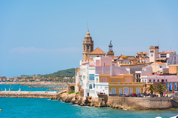 View of the historical center and the ñhurch of Sant Bartomeu and Santa Tecla in Sitges, Barcelona, Catalunya, Spain. Copy space for text. Isolated on blue background.