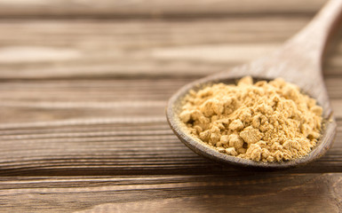 Ginger powder in wooden spoon on wooden table.