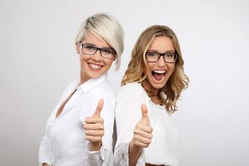 Zwei blonde Frauen mit Brille lachen und Daumen hoch