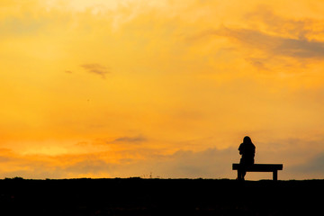 silhouette of woman relax on chair happy time sunset