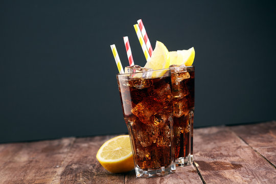 Softdrink with ice cubes, lemon and straw in glass