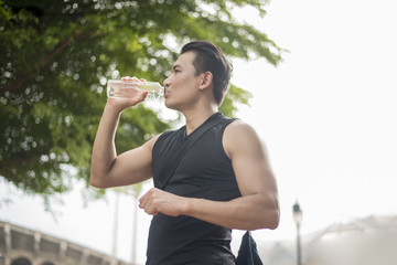 Sport man Drinking water at outdoor city