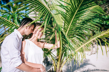 Young couple embrace each other near the fresh green palm tree.