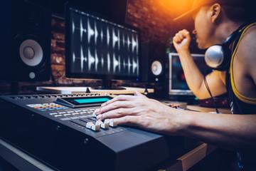 asian popular DJ working in radio broadcasting studio or music producer working in recording studio
