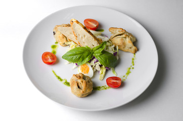 Salad with pies and lettuce leaves on a white plate