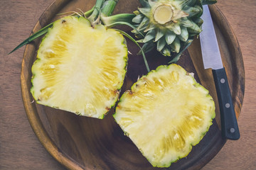 Fresh Pineapple cutting in wood plate on wooden table