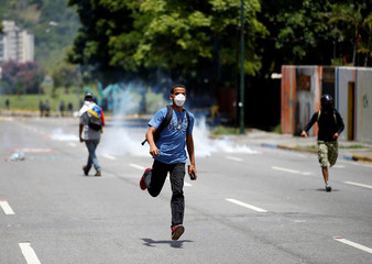 Demonstrators clash with riot security forces while participating in a strike called to protest against Venezuelan President Nicolas Maduro's government in Caracas