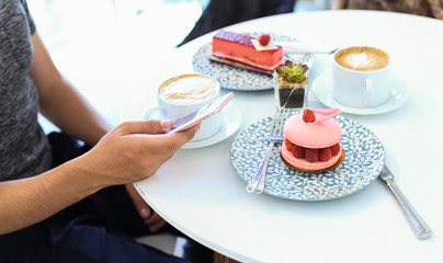 Man Holding Smartphone Texting Waiting for a Date at the Coffee Shop with Cup and Dessert