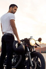 Sporty biker handsome rider male in white blank t-shirt walk to classic style cafe racer motorbike on rooftop at sunset. Vintage bike custom made in garage. Brutal urban lifestyle. Outdoor portrait.