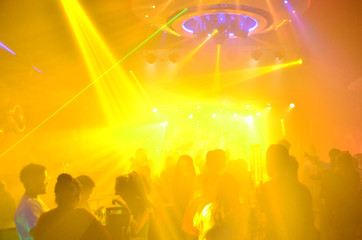 club party is blurred for background.Light in club party Show And Silhouette hands enjoying the club party with concert. Blurry night club DJ party people enjoy of music dancing sound .