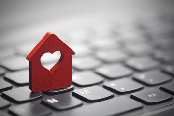 Small red house with heart over laptop keyboard