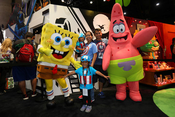 A family poses for a picture with cartoon character Sponge Bob during the opening day of Comic Con International in San Diego