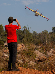 A man takes pictures of a Croatian firefighter plane as it drops water on forest fires in Lustica peninsula near Tivat, Montenegro