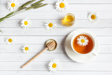 A Cup of chamomile tea and honey on white wooden background