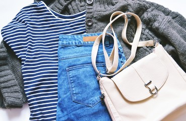 Flat lay fashion women's clothes photo/ Autumn and winter fashion blogger's outfit. Striped tshirt, brown wool knitted cardigan, blue jeans from denim and beige bag. Casual style, trendy wear