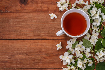 Cup of black tea and white Jasmine flowers on a brown wooden background