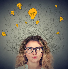 Thoughtful woman in glasses with many ideas light bulbs above head