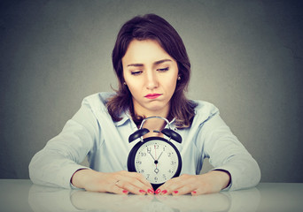 Sad bored woman with alarm clock sitting at table in her office