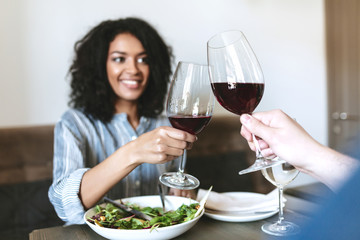 Young smiling girl drinking red wine in company at cafe. Pretty African American girl eating salad and drinking wine in restaurant. People drinking red wine in restaurant