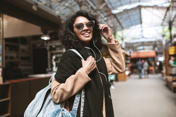Cool African American girl wearing sunglasses and earphones. Smiling girl with dark curly hair looking in camera on street. Nice girl in coat,scarf and bag on her shoulder walking around street
