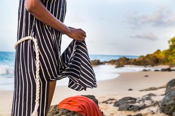 Woman in striped robe changing clothes on a tropical beach
