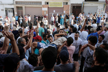 Protesters evacuate a man during a demonstration against alleged corruption in the town of Al-Hoceima