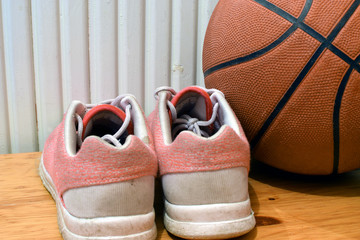 Sport shoes and basketball on wooden floor. Close up, square shape image.