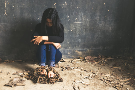 Trapped woman. Young woman trapped in chains covering face with hands while sitting on the floor in a dark room
