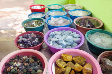 Various crude gems in a colorful baskets in a gemstone workshop